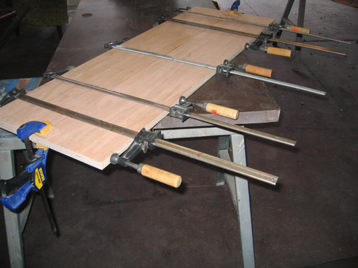 View of boards in clamped position after inserting biscuits and gluing.